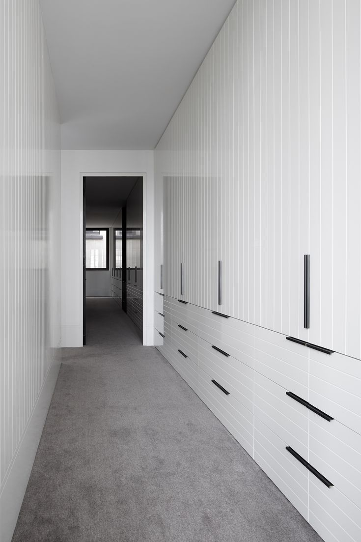 Walk in robe joinery covered in white painted v-groove boards. Direction is…