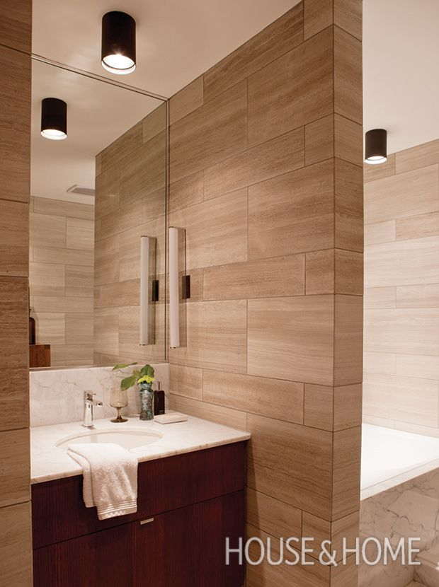 In this small bathroom, a light-reflecting frameless mirror and floor-to-ceiling Persian limestone creates a more open, seamless look. Photographer: Jean Longer   Designer: Alexandre Blazes and Benoit Gérard