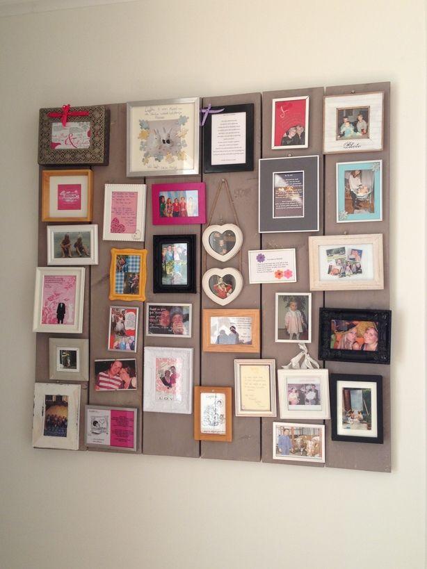 Collage van allerlei fotolijstjes op steigerhout. Leuk idee voor in de hal..