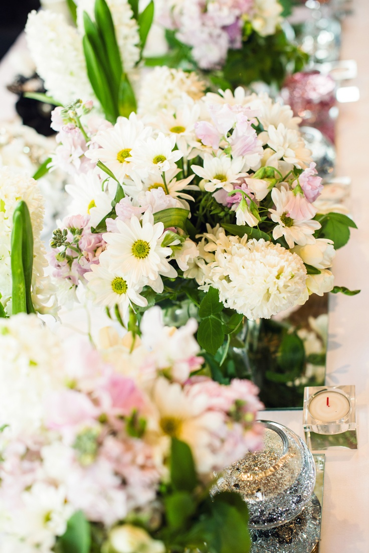 Fresh flowers, candles, glitter and sequined jars filled with lolly pops to match the girls bouquets scattered on every table.