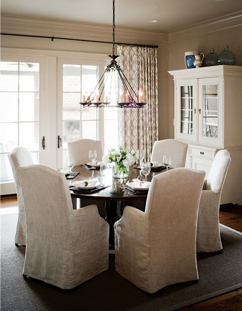 Laura Casey Interiors Kitchen. Ideas for dining area: French doors, patterned curtain panels, chairs with slips, circular table.  Love this!