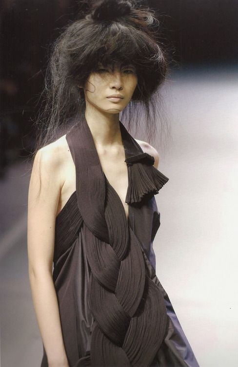 """Yohji Yamamoto S/S 2005. Không phải là nhà thiết kế Nhật Bản đầu tiên bước chân lên sàn diễn danh vọng Paris. Nhưng phải đến khi đội quân người mẫu không trang điểm, mặc đồ đen, đi giày đế phẳng của Yohji Yamamoto và Rei Kawakubo """"diễu hành"""" trên sàn diễn Paris, người ta mới nói đến một làn sóng mới, """"thời trang ý niệm"""", """"thời trang tri thức"""" hay """"phản thời trang"""""""