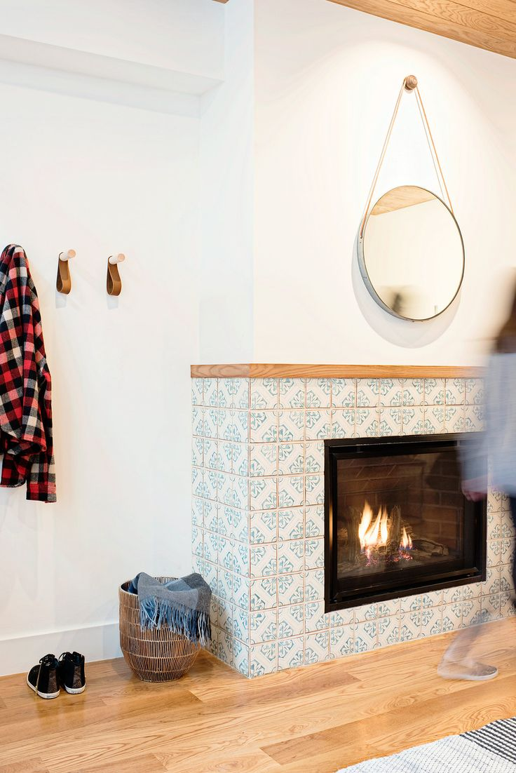 The fireplace features Ann Sacks patterned cement tile in royal blue and off white - fireplace look both exotic (with the tiles) and clean (again white wall)