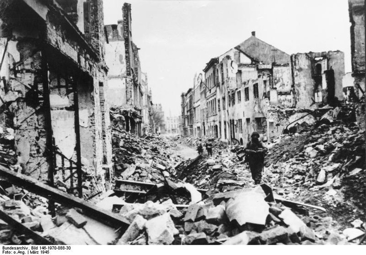 Soldiers of the Third U.S. Army walk in a debris-laden street of Coblenz, Germany,following capture of the city on March 17, 1945, after fierce street fighting. When the last group of German soldiers tried to surrender in the face of overwhelming U.S. advantage, Gestapo and SD men inside a nearby building opened fire of them.