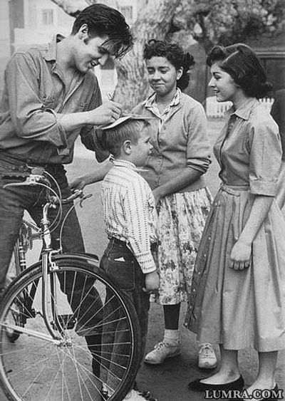 Elvis signing autographs on a bicycle