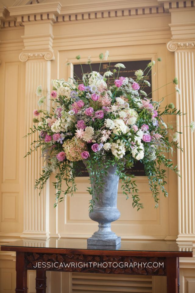 The altar arrangement was a large arrangement in one of our charcoal urns. The flowers included antique green hydrangea, blue scabiosa, Queen Anne's lace, white hydrangea, Italian ruscus, cool water roses, white and pink veronica, lavender, pink astilbe, and pink scabiosa. | by Dorothy McDaniel's Flower Market #wedding