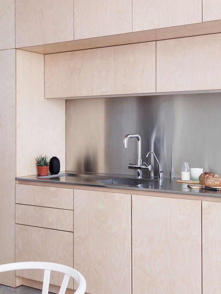 Kitchen Ideas - This contemporary kitchen has hardware-free light plywood kitchen cabinetry and a stainless steel backsplash and countertop.