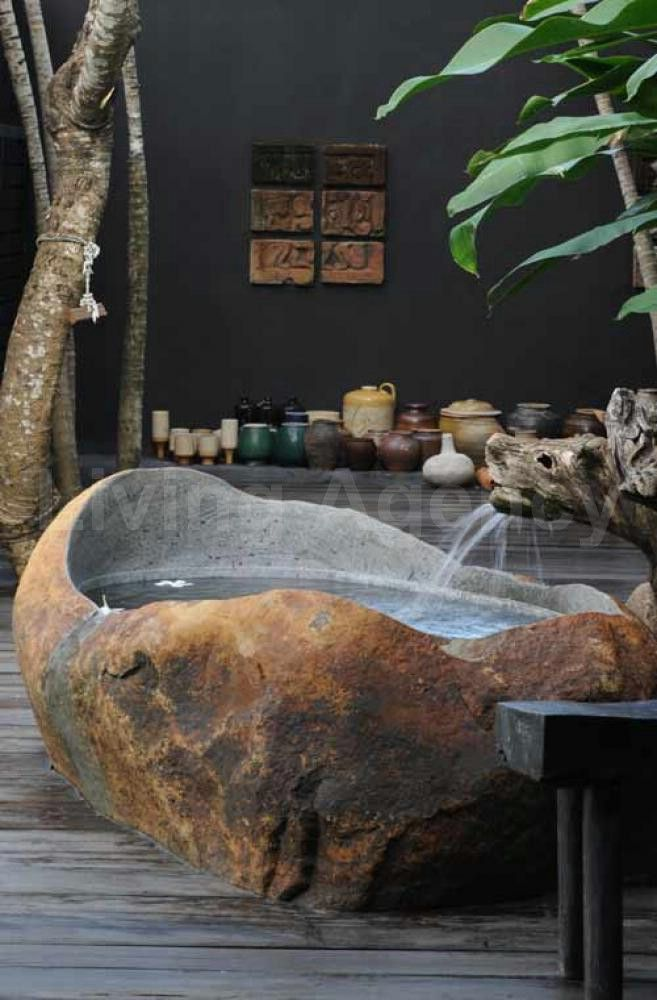 carved natural stone bathtub | outside living spaces being one with nature, what could be better