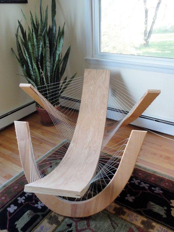 Lounge chair , pièce en bois maintenu par les fils qui lient les pièces entre elles en étant croisées.