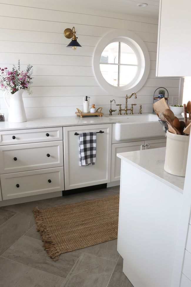 In this small space you must cover the dishwasher with cabinetry to make a seamless flow.