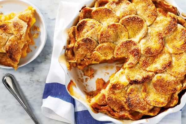 The Ultimate Peach Pie 6 cups sliced pitted peeled firm ripe peaches 3/4 cup granulated sugar 1/4 cup all-purpose flour 1 tbsp lemon juice 1 tsp vanilla 1 egg yolk 2 tsp coarse sugar, (optional) Pastry: 2 cups all-purpose flour 3 tbsp cornmeal 1/2 tsp salt 1/2 cup cold butter, cubed 1/2 cup cold lard, cubed 1/4 cup Ice water, (approx) 3 tbsp sour cream