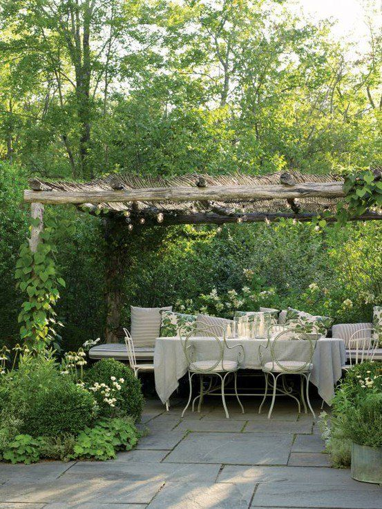 Love this garden terrace dining area shaded by a rustic arbor.