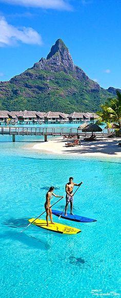 Honeymooners enjoying a Stand Up Paddle session in the blue lagoon of the InterContinental Resort & Thalasso Spa in Bora Bora | boraboraphotos.com