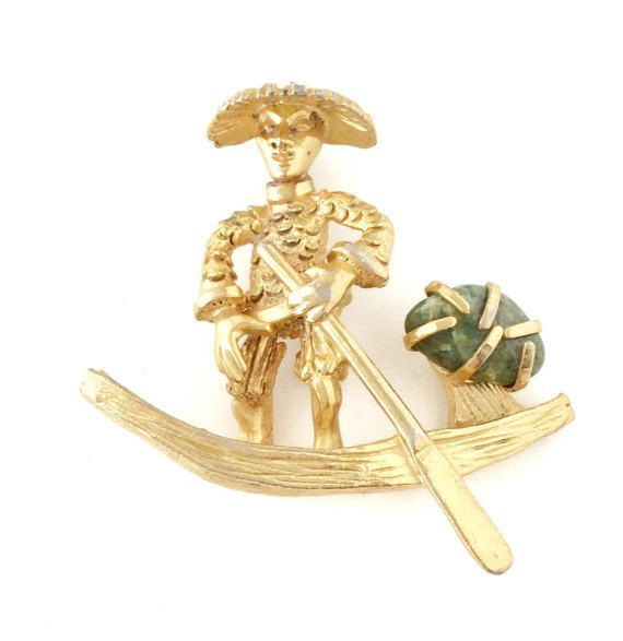 Take a closer look at the well details of this gorgeous and unique vintage 50s brooch. It features an Asian man in canoe with oar and green stone. It is made of gold tone metal. Locking pin back. Signed BSK. It is in excellent vintage condition. Measures approx. 2 long and approx. 1-3/4 at tallest. C. 1950s. It is a great piece to add to your vintage jewelry collection. You will love it!  Browse more of my vintage brooches and jewelry…