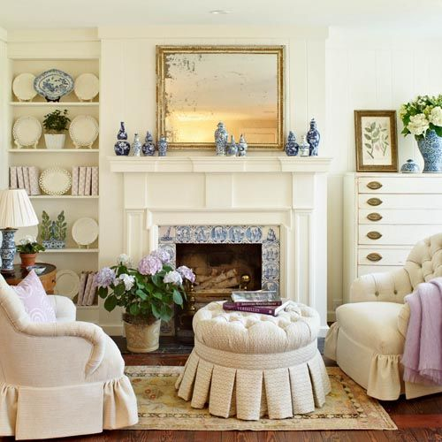 Neutral Living Room with blue and white jars, lamp, and Delft tiles at fireplace. by Knight Carr & Co.