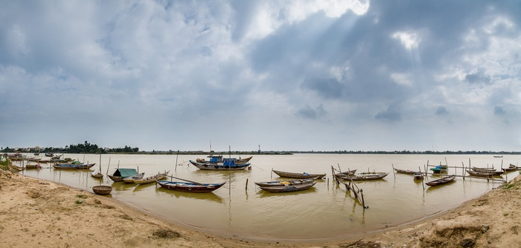 Fishing boats and trawls sit in the waters of the Thu Bon River