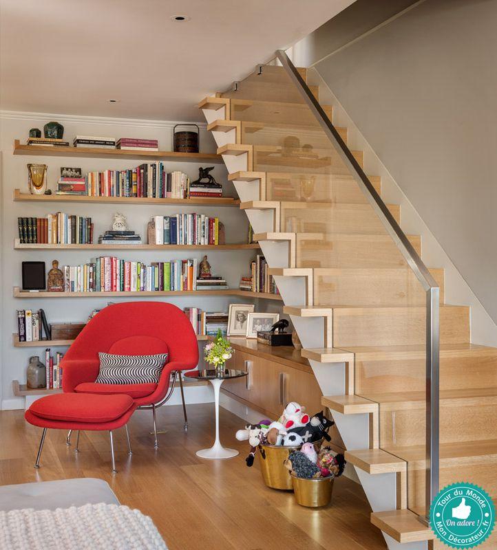 Un bel escalier moderne en bois blond et garde-corps en verre avec sa bibliothèque intégrée.