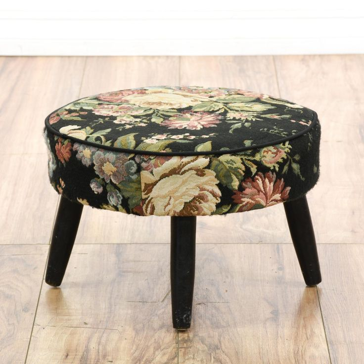 This cottage chic ottoman is upholstered in a durable woven tapestry fabric in a black floral print. This footstool has a round cushion top with tapered black mid century legs and piping trim. Adorable little stool perfect for a small armchair!  #cottagechic #chairs #ottoman #sandiegovintage #vintagefurniture