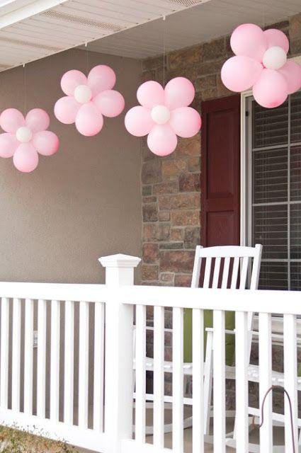 DIY: Knoop 5 grote ballonnen aan elkaar vast. Zet aan elke kant een kleine, witte of gele ballon vast. En dan ophangen.