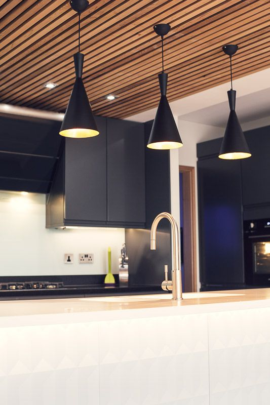 Beaut rose gold tap complementing the warm gold glow from the pendulum lights and rich cedar clad ceiling. Beautiful contrast with moulded white worktops and matt black units at edge24.co.uk