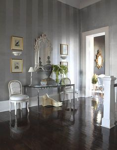 """A Silver Entrance Hall  Marshall wanted the second-floor entrance hall to be """"neutral, but not boring."""" He painted the walls with silver radiator paint, then added overscaled, soft, """"tarnished"""" stripes in a gray-tinted glaze for a """"subtly dramatic"""" effect. The foot sculpture is a plaster cast of the foot of Apollo."""