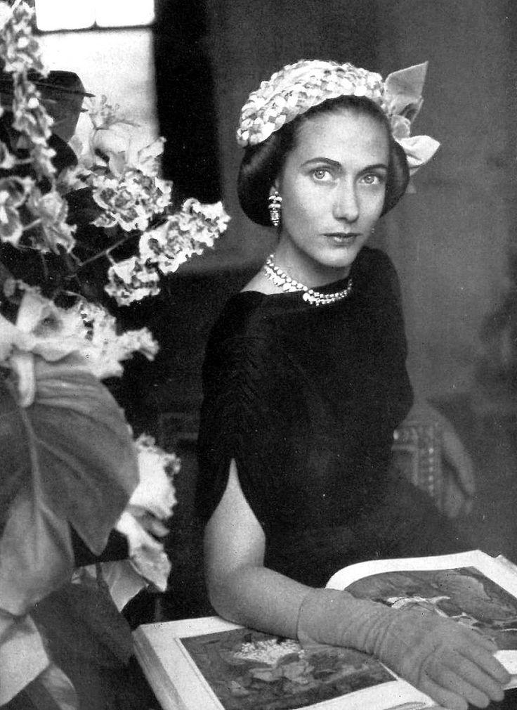 Madame (Hélène) Marcel Rochas reading in a hat by Caroline Reboux, Photo by Georges Saad, 1950.