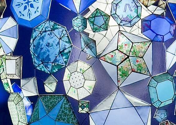 Massive, glowing webs of geometric gems climb the walls, successfully controlling the behavior of early afternoon light—while soaking the empty surfaces of the space with gentle washes of color. It's only upon close inspection that the pieces reveal themselves to be painstakingly handcraf