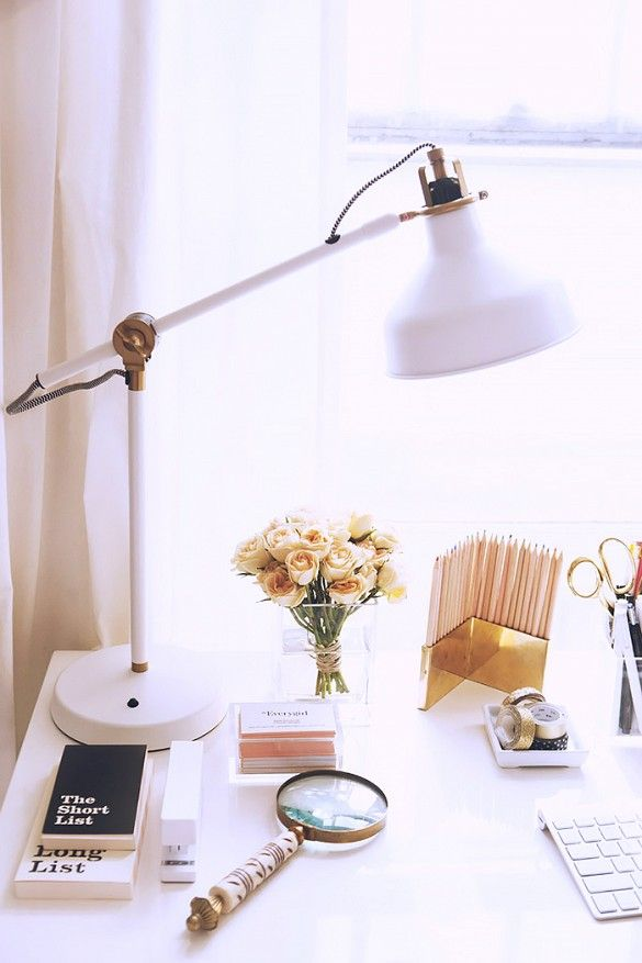 Styled desk with feminine accessories and modern table lamp