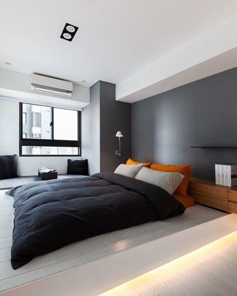 i like the modern look of this bedroom especially the rich gray wall color with the bright orange pillows
