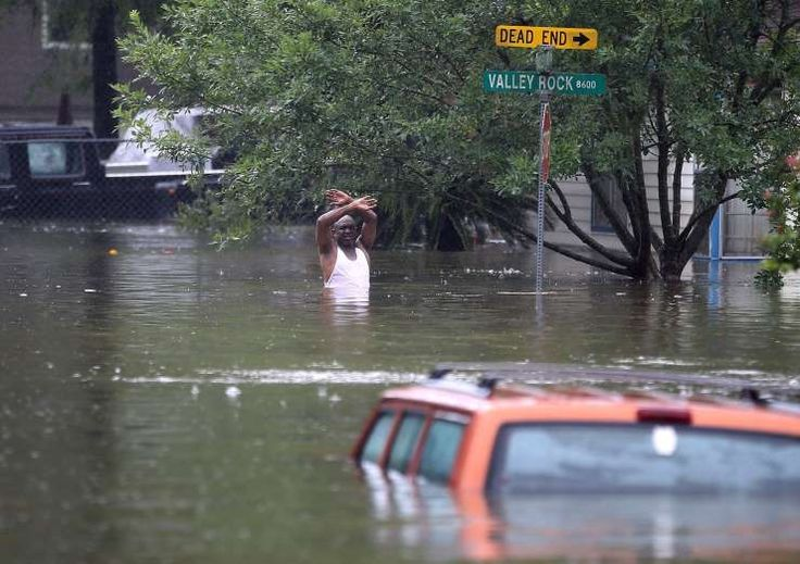 A man waves down a rescue crew as he tries to leave the area after it was inundated with flooding from Hurricane Harvey on Aug. 28, 2017 in Houston, Texas.