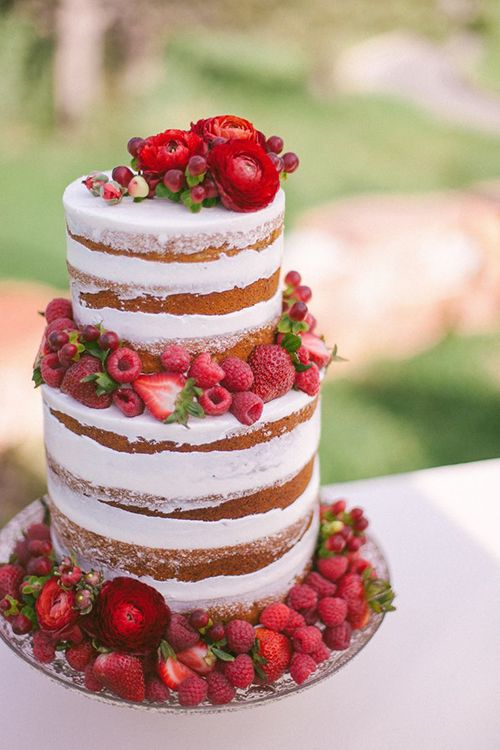 A naked wedding cake with fresh raspberries and strawberries, a handful of bright-red ranunculus buds, and red hypericum berries | Brides.com