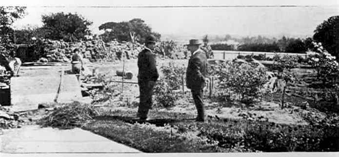 """PH 7820. At """"Leura"""", Toorak, Mr. Payne and reporter inspecting the pond which was being built especially for some water lillies which Mr. Payne had imported from abroad. The pond was only eighteen inches in depth, on account of the children; c.1904."""