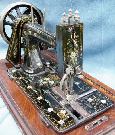 This elegant machine has no makers name but was probably made by Hengstenberg & Co. Note there is an additional slide plate on the bed.    It has Mother of Pearl flowers, swagged flowers and a bouquet to the centre bed. The base has an inlaid ruler, decorative marquetry and catch to hold the machine to the base.
