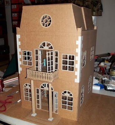 Amazing cardboard dollhouse. Look at those windows!! There are two towers in the back that slide out to make the house wider and open the back up for playing. Wow! That's one lucky little girl!