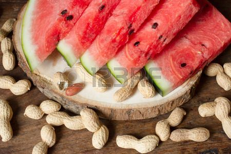 ripe red watermelon with peanuts on wooden background