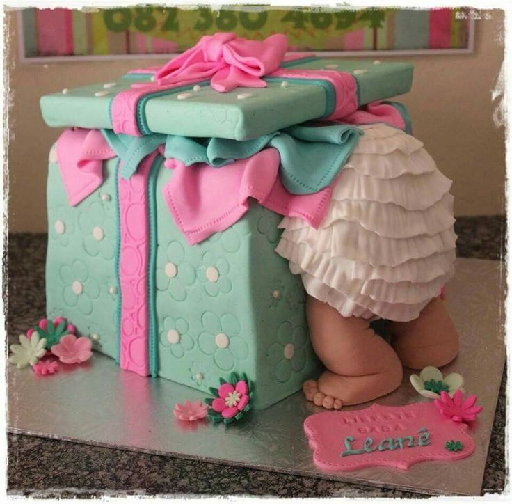 Baby peeking in package cake.