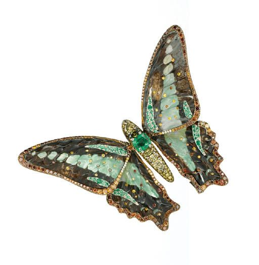 AN EXQUISITE COLOURED DIAMOND AND MULTI-GEM BUTTERFLY CLIP BROOCH, BY WALLACE CHAN Designed as a butterfly, the body set with a cushion-shaped tsavorite garnet and vari-cut yellow diamonds, to the butterfly specimen wings encased in carved rock crystal with mother-of-pearl back, enhanced by brilliant-cut yellow to brown diamond trim and accents, mounted in titanium