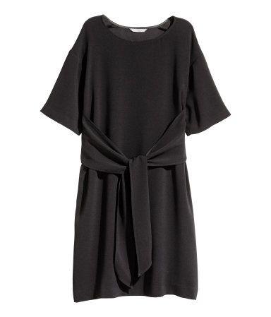 Schwarz. Kurzes Kleid aus Kreppstoff mit Bindebändern vorn. Das Kleid hat überschnittene Schultern, kurze Ärmel und eine gerade Passform. Ungefüttert.