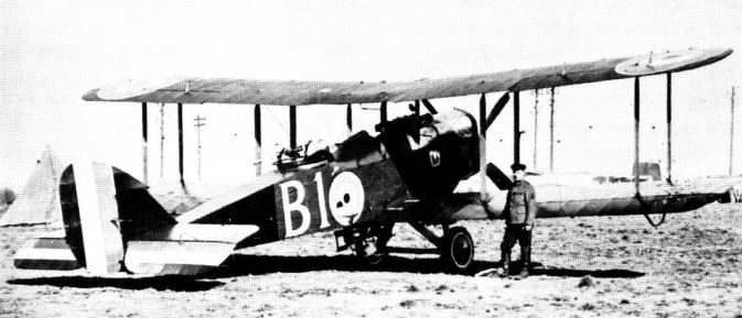 Full production-standard naval Eagle-powered D.H.4, N6000, with flat rear fuselage decking and flush-mounted rear Scarff gun ring. The aircraft is armed with twin front Vickers guns and is shown carrying a fuselage-mounted 112 lb RL bomb and eight wing-mounted light bombs. The repetition of the rudder flash on the elevators was unusual.