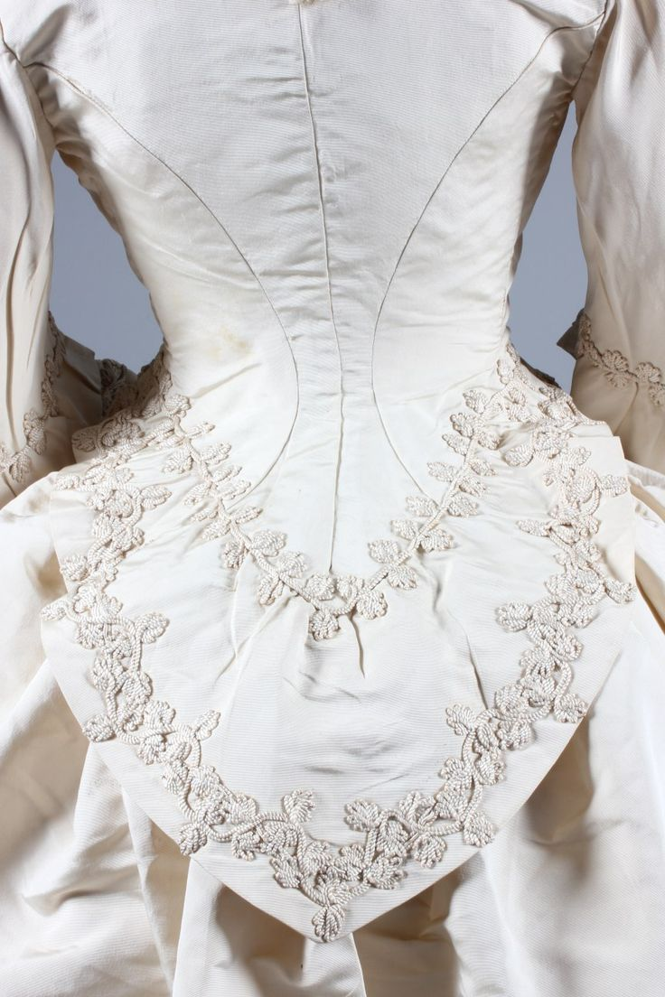 An ivory silk faille bridal gown, circa 1871, the bodice and waistband of skirt applied with 'Grand Magasins de la Paix' stamped labels, the bodice with bell-shaped sleeves, jacket-like bodice with curved basque, adorned with Brussels lace and ivory cord passementerie; the apron-type overskirt similarly adorned, over plain faille trained skirt with integral ruched gathers to the rear in the area to take a bustle. Detail