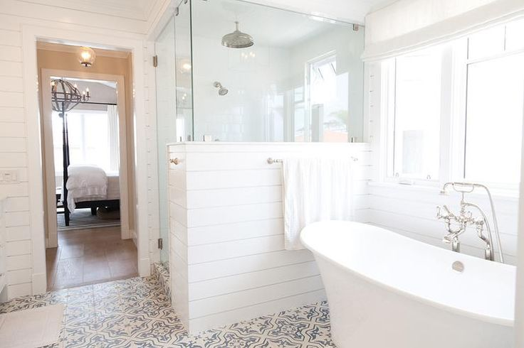 Cottage bathroom features a glass and shiplap shower enclosure fitted with a ceiling mount rain shower head positioned next to a freestanding tub and vintage style tub filler atop a white and blue mosaic tiled floor.