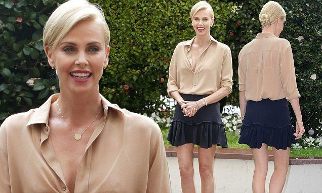 Charlize Theron parades her endless limbs in a ruffled navy mini skirt