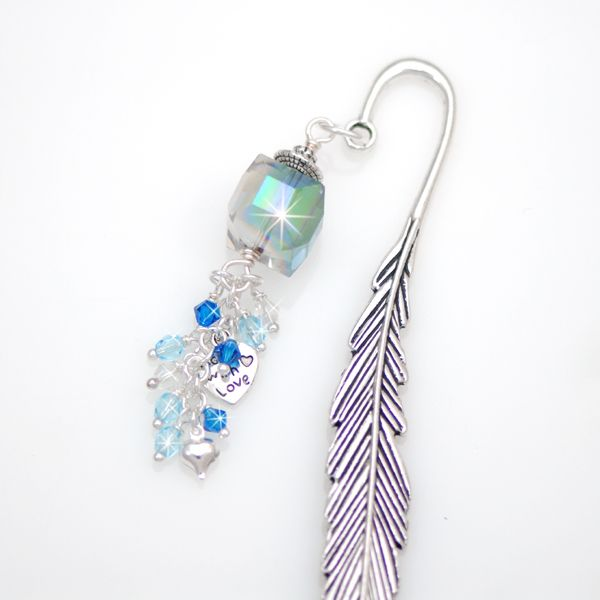 Bohemia Crystal Bookmark - If you are giving a book as a gift you can include a bookmark to personalize it. This will show how much thought and care you put into choosing their gift.  The Bohemia bookmark is crafted with a gorgeous metal feather effect shepherd's hook and is embellished with a large stunning vibrant crystal cube and a waterfall of sparkling crystals in soft sky blue, deep cobalt blue and clear.