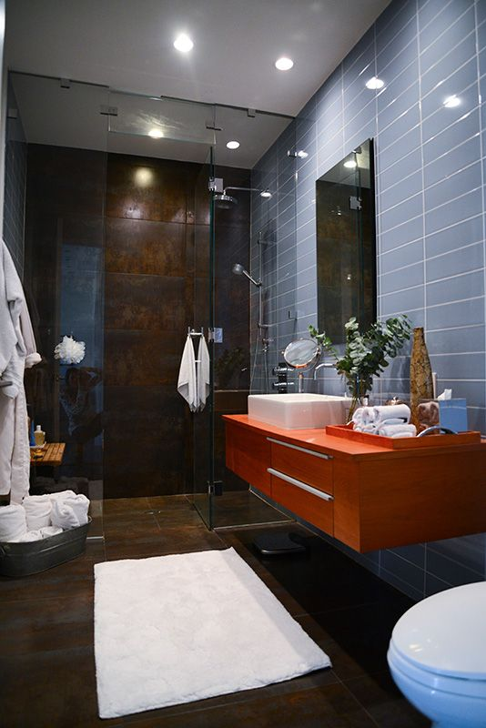 We love the console's pop of orange against the dark backdrop of the bathroom. Masculine and sleek, this bathroom is perfect inspiration for those seeking contemporary, urban design.