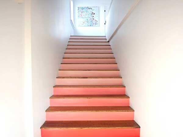 La couleur rose saumon des contres marches réveille la déco blanche de cette cage d'escalier. Une idée déco à refaire avec une couche de peinture de couleur vive