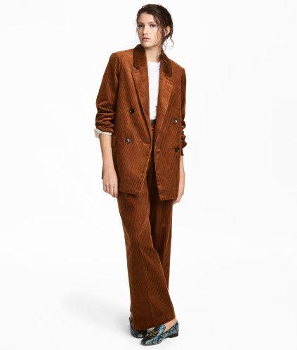 Brun. En bukse i bomullscord med gylf med glidelås og skjult hempe. Sidelommer, falske passpolerte baklommer og rette, vide ben med legg øverst og press