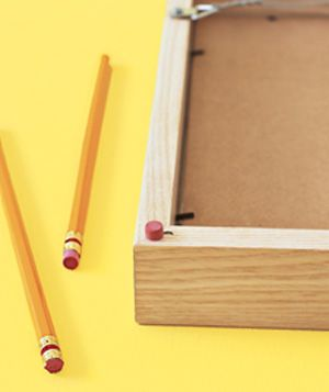 Keep picture frames from rubbing against the wall and damaging it by gluing an eraser to the corners of the frame