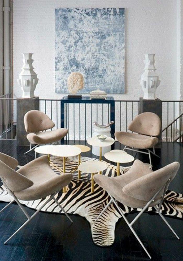 deco zebre avec un tapis de zebre, chaises de salon beiges, peintures muraux