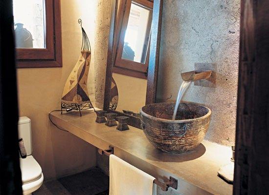 Para darle un toque original, se transformo un cuenco de madera tipo vasija, en una original bacha. Al costado, un espejo con marco de madera y diferentes adornos.