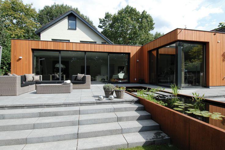Uitbouw met hout en aluminium. Deze uitbouw is erg strak vormgegeven. De rechte lijnen lopen mooi door in de tuin. De uitbouw is zowel brandwerend, onderhoudsarm als inbraakwerend. Reynaers